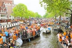 AMSTERDAM - 26. APRIL: Amsterdam-Kanäle voll von Booten und von Leuten Stockfoto