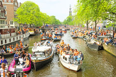 AMSTERDAM - APRIL 26: Amsterdam kanaler mycket av fartyg och folk Arkivbilder