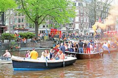 AMSTERDAM - APRIL 26: Canals of Amsterdam full of people in oran Stock Photo