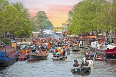 AMSTERDAM - APRIL 26: Amsterdam canals full of boats and people. In orange during the celebration of kings day on April 26, 2014 in Amsterdam, The Netherlands Royalty Free Stock Photography