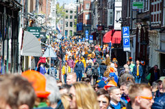 AMSTERDAM-APRIL 27: Crowd of people on Amsterdam busy street celebrate King's Day on April 27,2015, the Netherlands. Stock Photo