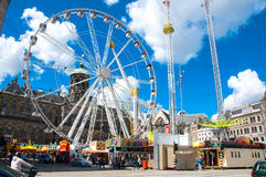 AMSTERDAM-APRIL 30: Dam Square with big wheel and Royal Palace on the background on April 30, 2015 in Amsterdam, Netherlands. Stock Images