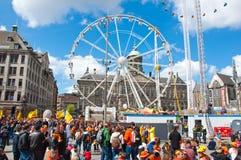 27 Amsterdam-APRIL: Damvierkant met Reuzenrad en Royal Palace op de achtergrond tijdens de Dag van de Koning Stock Foto