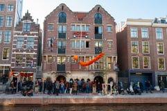27 Amsterdam-APRIL: De beroemde Buldog van Amsterdam coffeeshop en het hotel in rosse buurt, mensen vieren de Dag van de Koning Royalty-vrije Stock Fotografie