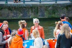 27 Amsterdam-APRIL: De gelukkige Plaatselijke bewoners en de toeristen in sinaasappel hebben pret op een boot tijdens de Dag van  Stock Afbeelding
