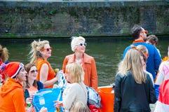 27 Amsterdam-APRIL: De gelukkige Plaatselijke bewoners en de toeristen in sinaasappel op een boot vieren de Dag van de Koning op  Royalty-vrije Stock Fotografie
