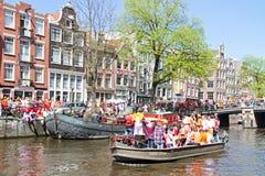 AMSTERDAM - APRIL 30: De kanalenhoogtepunt van Amsterdam van boten en mensen Stock Afbeelding