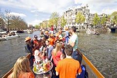 AMSTERDAM - APRIL 30: De kanalenhoogtepunt van Amsterdam van boten en mensen Royalty-vrije Stock Afbeeldingen