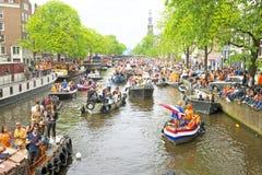 AMSTERDAM - APRIL 26: De kanalenhoogtepunt van Amsterdam van boten en mensen Royalty-vrije Stock Fotografie