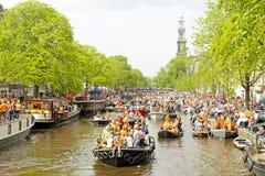 AMSTERDAM - APRIL 26: De kanalenhoogtepunt van Amsterdam van boten en mensen Royalty-vrije Stock Foto