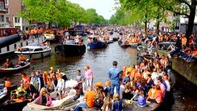 AMSTERDAM - APRIL 26: De kanalenhoogtepunt van Amsterdam van boten en mensen in sinaasappel tijdens de viering van kingsday op 26 stock video