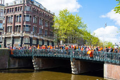 27 Amsterdam-APRIL: De menigte van mensen let op het festival over de brug tijdens de Dag van de Koning (Koningsdag) op 27 April, Royalty-vrije Stock Foto's