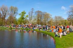 27 Amsterdam-APRIL: De menigte van plaatselijke bewoners en de toeristen in sinaasappel vieren binnen de Dag van de Koning op 27, Stock Foto's