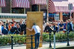 27 Amsterdam-APRIL: De mensen bekijken het werpen van eieren in het gezicht (het vermaak van Amsterdam) tijdens de Dag van de Kon Stock Foto