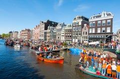 27 Amsterdam-APRIL: De mensen in sinaasappel op boten nemen aan de Dag van de vierende Koning deel door Singel-kanaal op 27,2015  Royalty-vrije Stock Foto's