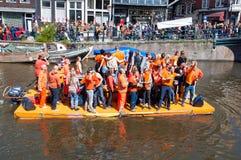 27 Amsterdam-APRIL: De mensen in sinaasappel vieren de Dag van de Koning langs het Singel-kanaal op het vlot op 27,2015 April Royalty-vrije Stock Afbeelding