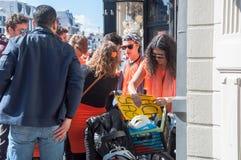 27 Amsterdam-APRIL: De niet geïdentificeerde vrouw verkoopt lachgas op de straat van Amsterdam aan jonge mannen tijdens de Dag va Stock Fotografie