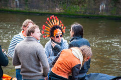 27 Amsterdam-APRIL: De niet gedefiniëerde mensen in traditionele sinaasappel vieren de Dag van de Koning op het Singel-kanaal op  Stock Afbeeldingen