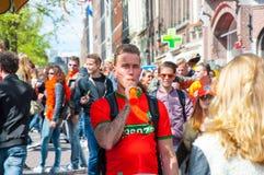 27 Amsterdam-APRIL: De niet gedefiniëerde persoon speelt de pijp, heeft de menigte van Mensen pret op de straat van Amsterdam tij Stock Foto's