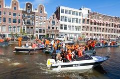 27 Amsterdam-APRIL: De plaatselijke bevolking en de toeristen op de boten nemen aan de Dag van de vierende Koning deel door Singe Stock Afbeelding