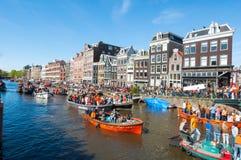 27 Amsterdam-APRIL: De plaatselijke bevolking en de toeristen op de boten nemen aan de Dag van de vierende Koning deel door Singe Royalty-vrije Stock Fotografie