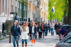 27 Amsterdam-APRIL: De plaatselijke bewoners en de toeristen gaan onderaan de bank van het Singel-kanaal de Dag van de Koning op  Royalty-vrije Stock Afbeelding
