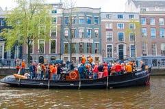 27 Amsterdam-APRIL: De plaatselijke bewoners en de toeristen hebben danspartij op de Dag van een bootkoning langs het Singel-kana Royalty-vrije Stock Foto's