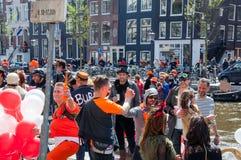 27 Amsterdam-APRIL: De plaatselijke bewoners en de toeristen hebben pret op een boot tijdens de Dag van de Koning, het Singel-kan Stock Afbeelding
