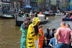 27 Amsterdam-APRIL: De plaatselijke bewoners en de toeristen plechtig vieren de Dag van de Koning langs het Singel-kanaal op 27,2 Stock Afbeeldingen