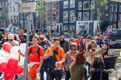27 Amsterdam-APRIL: De plaatselijke bewoners en de toeristen in sinaasappel hebben pret op een boot tijdens de Dag van de Koning, Stock Foto