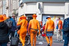 27 Amsterdam-APRIL: De plaatselijke bewoners en de toeristen in sinaasappel nemen bij viering Koningsdag (de Dag van de Koning) o Stock Afbeelding