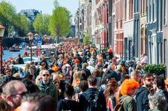 27 Amsterdam-APRIL: De plaatselijke bewoners en de toeristen vieren de Dag van de Koning langs het Singel-kanaal op 27,2015 April Stock Foto's