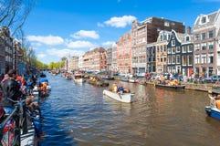 27 Amsterdam-APRIL: De plaatselijke bewoners en de toeristen vieren de Dag van de Koning langs het Singel-kanaal op zonnige dag o Royalty-vrije Stock Foto