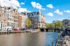 Amsterdam-April 30: Den Rokin kanalen med cyklar som parkeras längs banken, hotellet de l'Europe, är synlig i bakgrunden arkivfoton