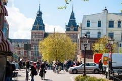 AMSTERDAM-APRIL 30: Det lokala folket rider cyklar på den Amsterdam gatan, Rijksmuseumen är synligt i bakgrunden arkivbild