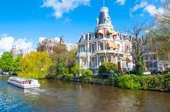 Amsterdam-April 30: Fartyg som kryssar omkring på den Amsterdam Singelgrachtkering kanalen på April 30,2015, Nederländerna Fotografering för Bildbyråer