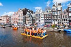 AMSTERDAM 27. APRIL: Glückliche Menschen feiern Day Königs entlang dem Singel-Kanal auf dem orange Floss 27,2015 im April Stockfotos
