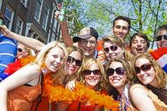 AMSTERDAM - APRIL 30: Grupp av vänner i apelsin som festar på Fotografering för Bildbyråer