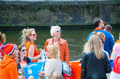 AMSTERDAM-APRIL 27: Happy Locals and tourists in orange on a boat celebrate King's Day on Amsterdam canal on April 27,2015, the Ne Royalty Free Stock Photography