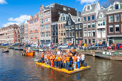AMSTERDAM-APRIL 27: Happy People celebrate King's Day along the Singel canal on the orange raft, crowd enjoy the festival. Royalty Free Stock Photography