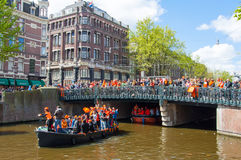 AMSTERDAM-APRIL 27:  King's Day also known Koningsdag on the Singel canal,  people watch the festival on the bridge. Royalty Free Stock Photography
