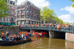 AMSTERDAM-APRIL 27:  King's Day (Koningsdag) boating on the Singel canal,  crowd of people watch the festival on the bridge on Apr Royalty Free Stock Photography
