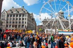 27 Amsterdam-APRIL: Menigte van mensen op Damvierkant en Royal Palace op de achtergrond tijdens de Dag van de Koning op 27 April, Stock Afbeelding