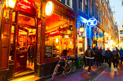 AMSTERDAM-APRIL 27: Nightlife on Amsterdam narrow street around red light district on April 27,2015, the Netherlands. Royalty Free Stock Images