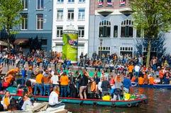 27 Amsterdam-APRIL: Partijboot op Singel-kanaal met menigte van mensen op de straat tijdens de Dag van de Koning op 27,2015 April Stock Fotografie