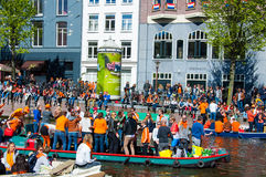 AMSTERDAM-APRIL 27: Party Boat on Singel canal with crowd of people on the street during King's Day on April 27,2015. Stock Photography