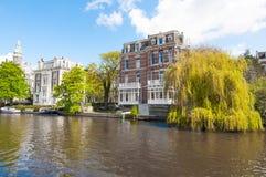 Amsterdam-April 30: Singelgrachtkering kanal med en härlig byggnad på April 30,2015, Nederländerna Royaltyfria Bilder