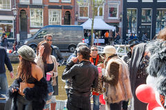 AMSTERDAM-APRIL 27: Unidentified people in the sunny day at the open-air party celebrate King's Day on the Singel canal. Royalty Free Stock Photography