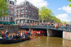 27 Amsterdam-APRIL: Van de koning het de Dag (Koningsdag) roeien op het Singel-kanaal, menigte van mensen let op het festival ove Royalty-vrije Stock Fotografie