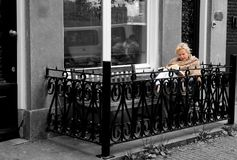 Reading a Book, Street Balcony, Nordic Outdoor Lifestyle, Beautiful Elder Blonde Woman, Amsterdam. Amsterdam, 2010 - Beautiful elder blonde woman bundled up and royalty free stock photography